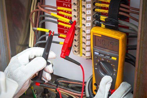 una mano con un guanto con in mano una pinza nera e una rossa attaccata a un quadro elettrico di un tester