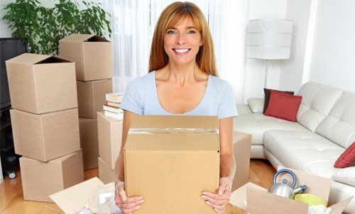 Woman with packed cartons ready for relocation