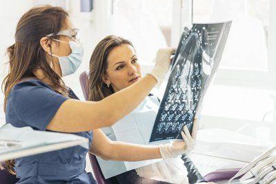 medico controlla una radiografia insieme a una paziente