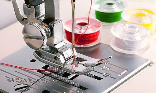 un ago di una macchina da cucire e dei rocchetti con dei fili colorati