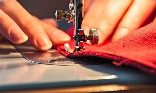 due mani che tengono ferme una stoffa mentre un ago cuce