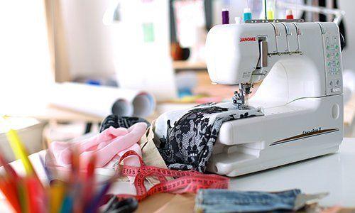 un centimetro rosso e una macchina da cucire che cuce un tessuto bianco a disegni neri