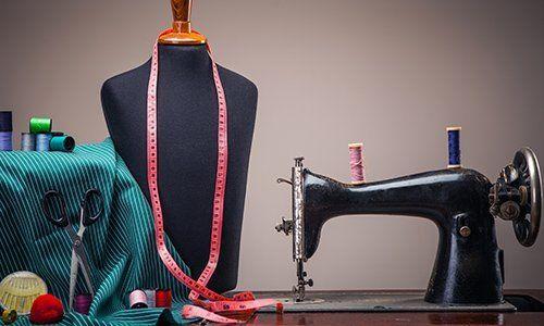 una macchina da cucire antica, un manichino con un centimetro e delle forbici