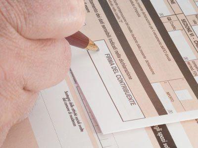 mano di una persona che scrive su un modulo per la dichiarazione dei redditi