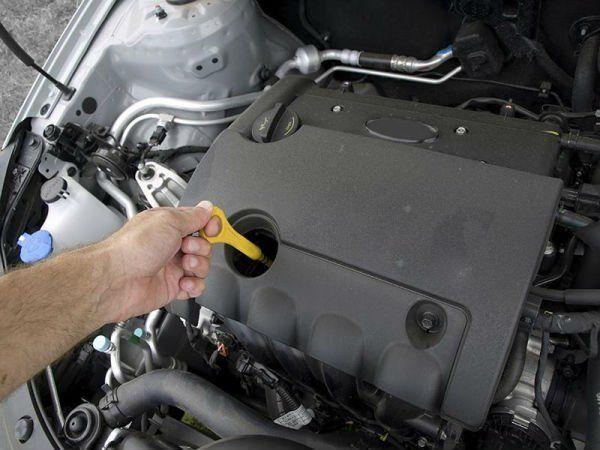 una mano che controlla l'olio del motore di una macchina