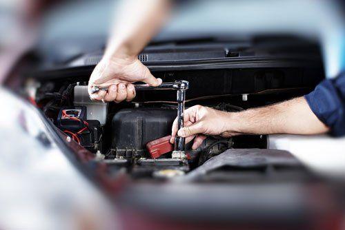 due mani con una chiave mentre svitano un bullone di un  motore di una vettura