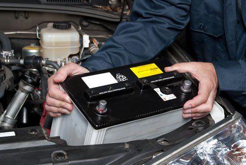 due mani di un meccanico che estraggono la batteria da una macchina