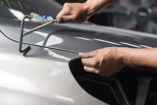 due mani con un attrezzo vicino a un cofano di una macchina grigia