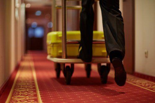 due piedi che spingono un carrello con una valigia