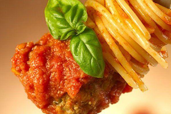 una polpetta con degli spaghetti e del basilico