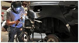 meccanico con casco integrale durante un lavoro di saldatura sul corpo di una automobile