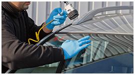 meccanico con tuta da lavoro e guanti sistema un parabrezza di un auto