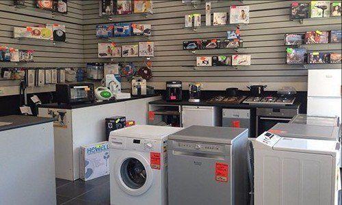 interno di un negozio con lavatrici e ferri da stiro