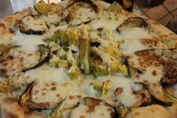 una pizza bianca con delle verdure