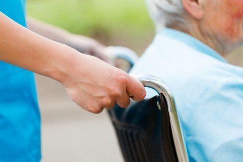 Mani che spingono la sedia a rotelle di un anziano