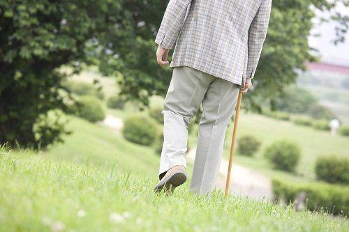 Uomo camminando per il campo con l'aiuto di un bastone