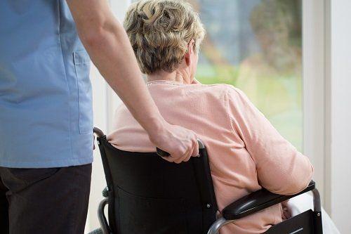 Uomo giovane spingendo la sedia a rotelle di una donna maggiore