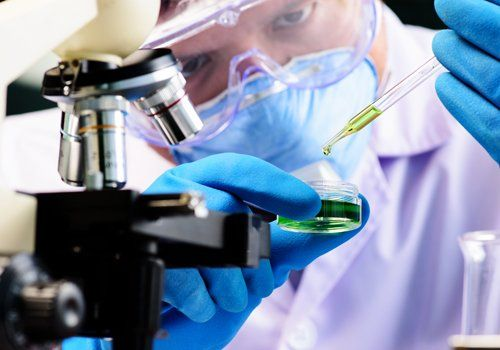 persona in laboratorio mentre esamina un campione