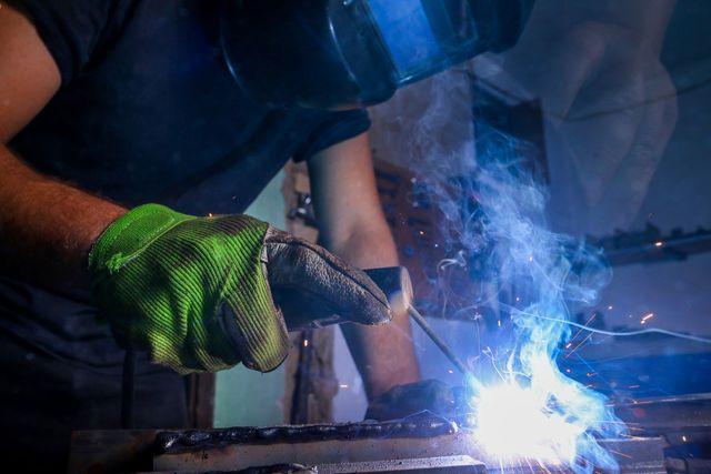 un carpentiere con la maschera durante un lavoro di saldatura