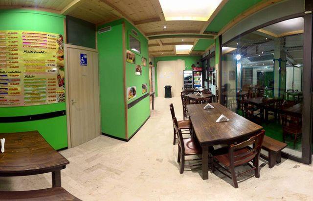 interno di una pizzeria con tavoli e sedie in legno