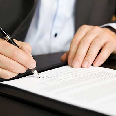 Businessman in dark suit and blue shirt sitting at office desk signing a contract with shallow focus on signature.