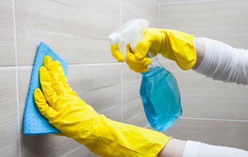Donna pulisce delle piastrelle con strofinaccio e spruzzino