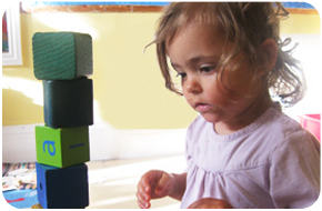 A little girl playing with building blocks