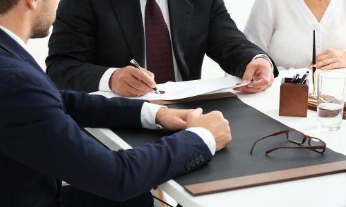 degli uomini seduti a un tavolo di cui uno che scrive su un foglio
