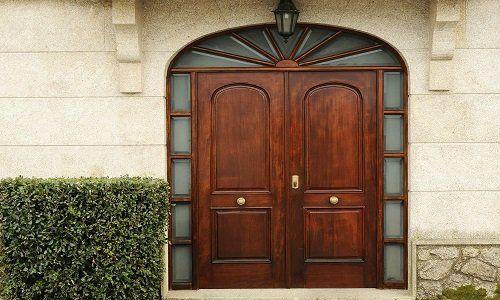 una porta da esterno in legno con dei pannelli di vetro intorno