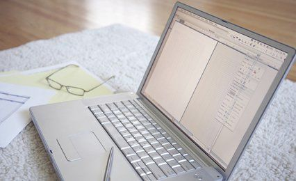 A silver lap top, glasses and sheets of figures on a table