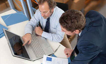 Two men looking at a lap top screen
