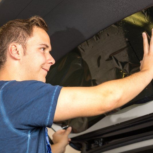 Our team member performing window tinting services on a car.