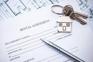 Rental agreement document with keys and silver pen
