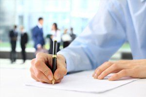 blue shirted arm on desk, hand with pen on paperwork