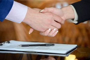man and woman shake hands over paperwork