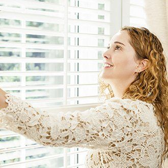 Smiling woman drawing her Venetian blinds