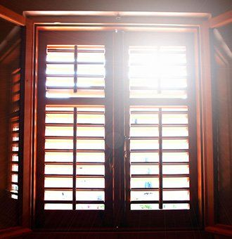 Sun shining through some wooden shutters