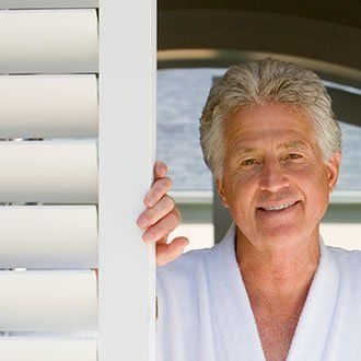 Smiling man leaning on a faux wood shutter