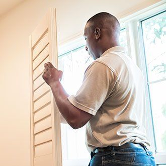 Man fitting wooden shutters to a window
