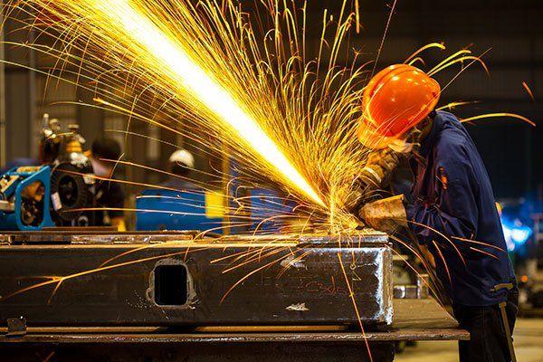 un uomo con un elmetto mentre usa un flex su un telaio di ferro