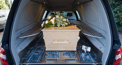 una bara in legno con sopra un mazzo di fiori bianchi all'interno di un carro funebre