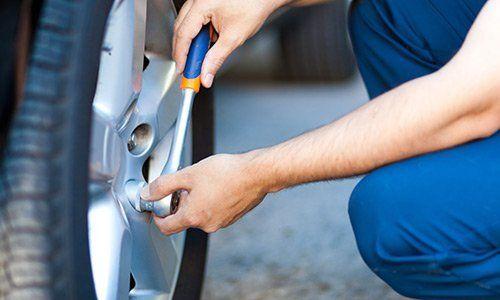 Braccia di meccanico che stringe bulloni di una ruota.