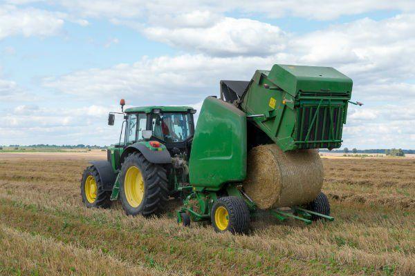 un trattore con un macchinario che fa delle balle di fieno