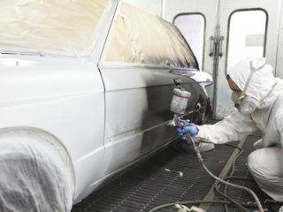Meccanico dipingendo un'automobile di bianco