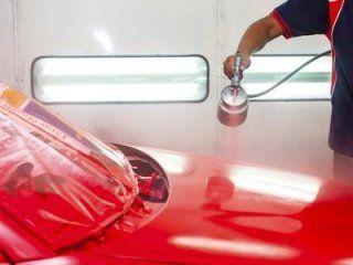 Meccanico dipingendo un'automobile di rosso
