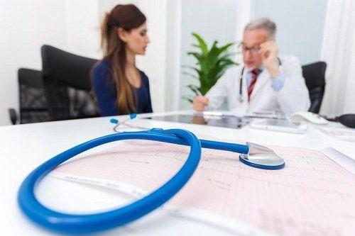 uno stetoscopio e un medico seduto vicino a una donna
