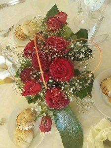 vaso di rose rosse su un tavolo allestito per una cerimonia