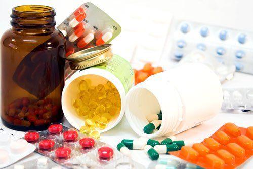 dei contenitori in plastica con dentro delle pastiglie e dei blister di pillole