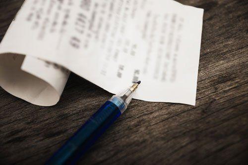 una penna blu appoggiata su un tavolo di legno accanto uno scontrino fiscale