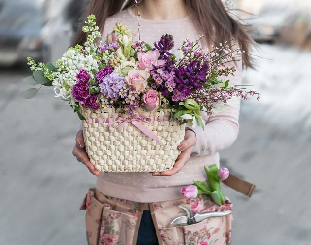 the florist holds beautiful basket of flowers